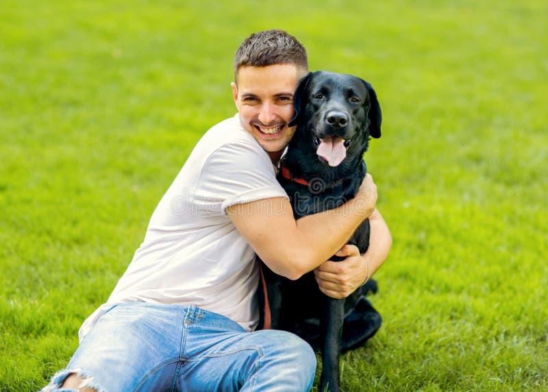 Grabb som kramar med hans hund labrador som spelar i parkera arkivfoton