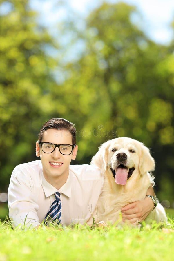 Grabb som ligger på ett gräs och kramar hans hund i en parkera fotografering för bildbyråer
