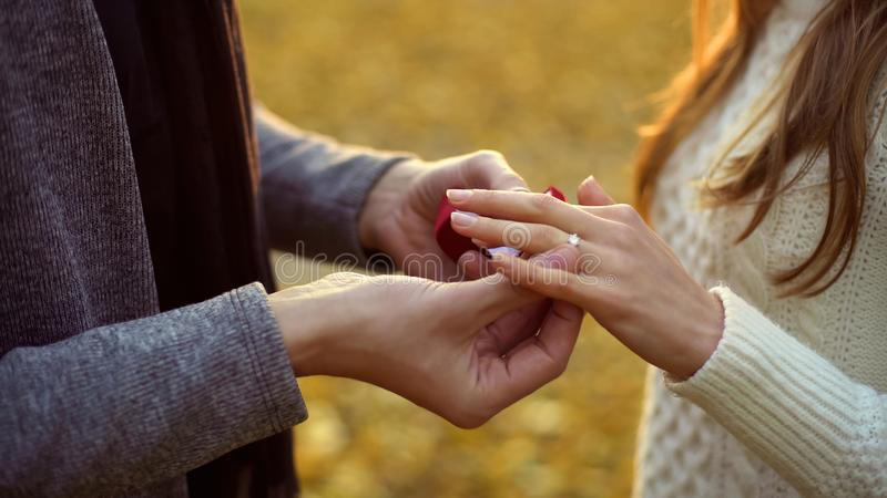Grabb som sätter den härliga diamantcirkeln på fingret av hans brud, allvarligt förhållande royaltyfri foto