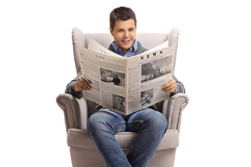 Grabb som sitter i en fåtölj och läser en tidning royaltyfri foto