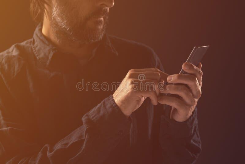 Grabb som skriver textmeddelandet på mobiltelefonen fotografering för bildbyråer