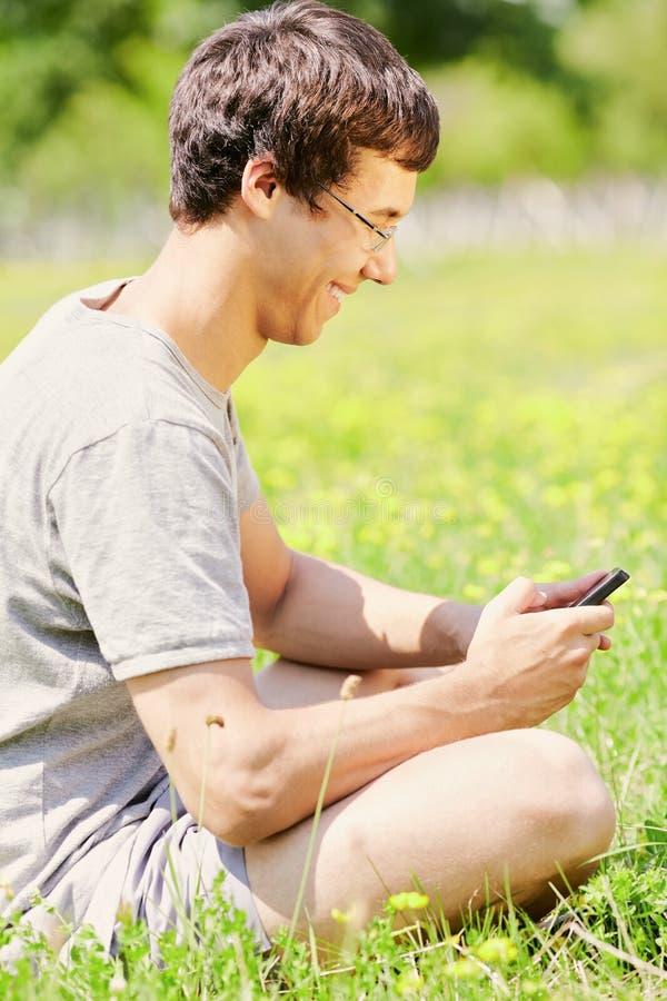 Grabb som smsar på mobiltelefonen arkivfoton