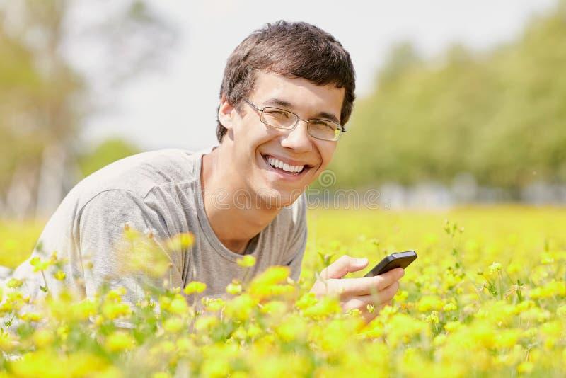 Grabb som smsar på mobiltelefonen royaltyfria foton