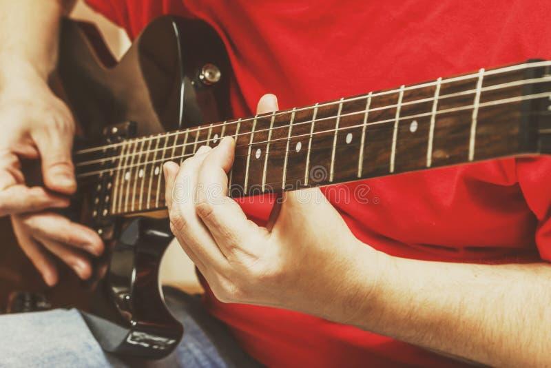 Grabb som spelar den elektriska gitarren royaltyfria foton