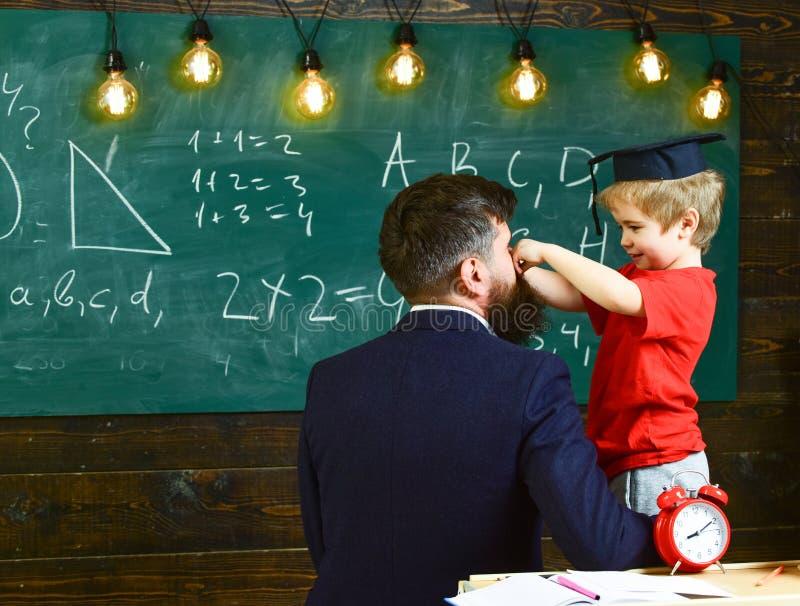 Grabb som tillbaka vänds, och liten unge i klassrumet Gullig pojke som spelar med mustaschen av mannen Le barnet i avläggande av  arkivfoto