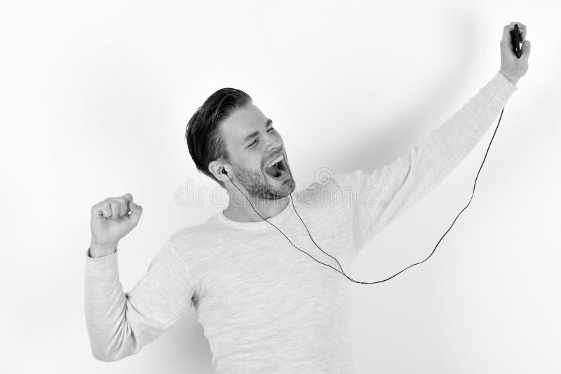 Grabballsånger och danser Gladlynt ung man som använder hörlurar och lyssnar till musik royaltyfri foto