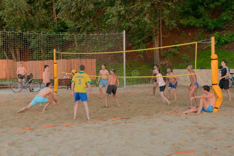 Grabbar och en flickalekvolleyboll på stranden Cheboksary Ryssland royaltyfri bild