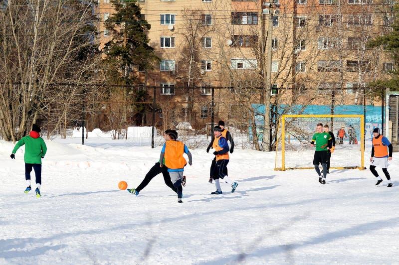 Grabbar spelar fotboll på ett fält som täckas med snö royaltyfria bilder