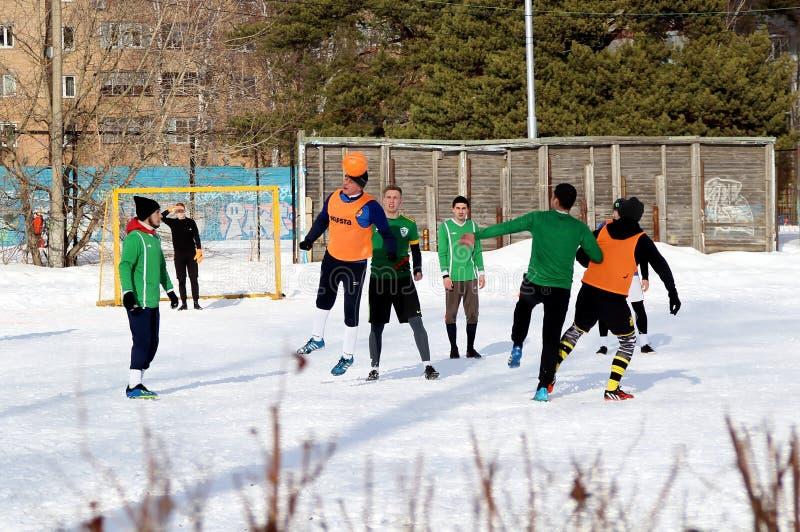Grabbar spelar fotboll p? ett f?lt som t?ckas med sn? royaltyfri fotografi
