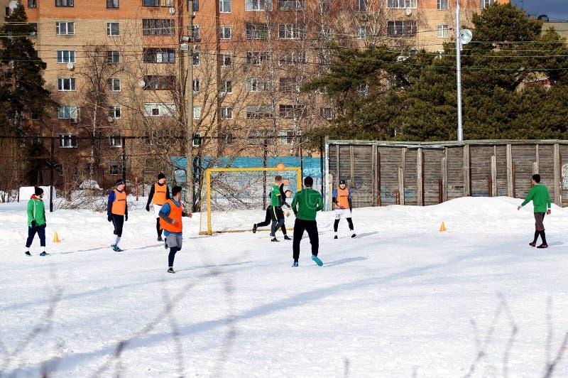 Grabbar spelar fotboll p? ett f?lt som t?ckas med sn? fotografering för bildbyråer
