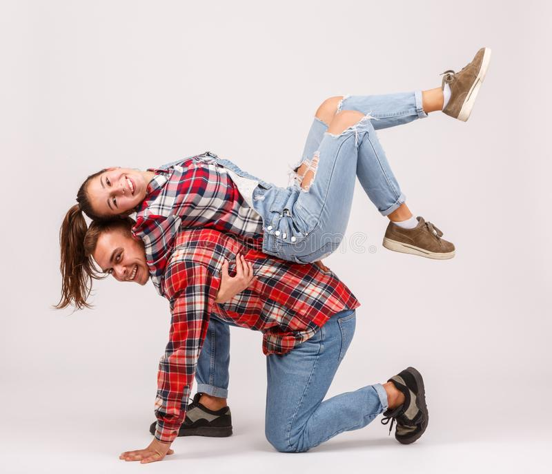 Grabben är på ett knä, och flickan ligger på hans tillbaka närbild på en grå bakgrund royaltyfria foton