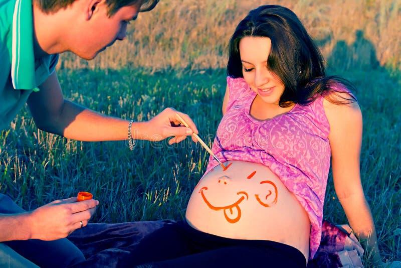 Grabben drar en framsida på en mage av gravida kvinnan royaltyfri bild