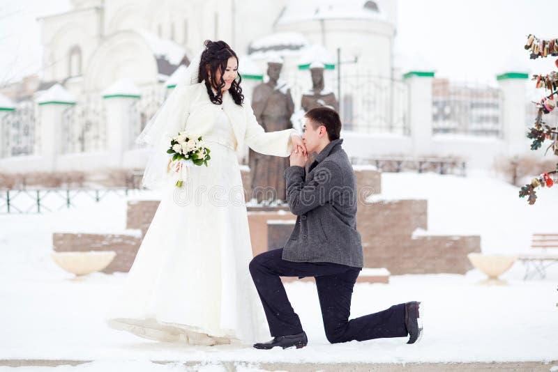 Grabben frågar flickahänderna Övervintra bröllop, brudgum på hans knä framme av bruden en snöig gata Förbindelsebegreppet royaltyfri foto
