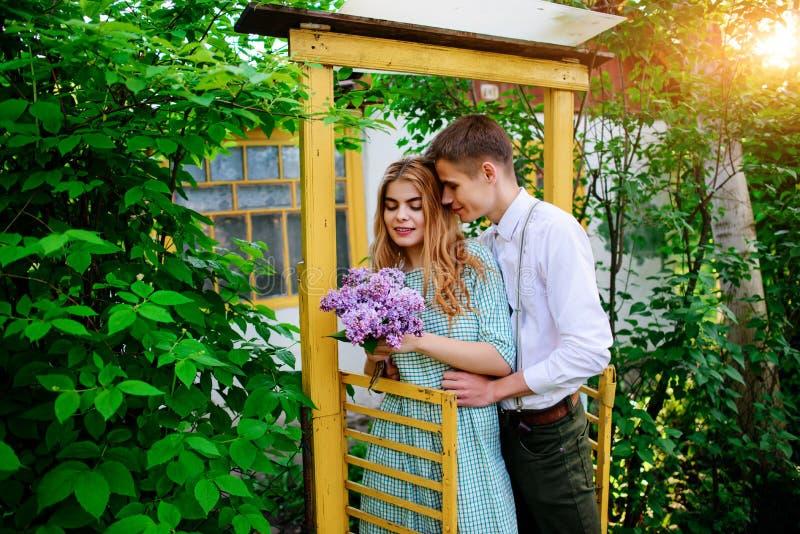 Grabben ger hans flickvän en bukett av lilor, henne kom ut ur porten arkivfoton