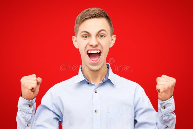 Grabben i den blåa skjortan jublar seger som isoleras på röd bakgrund, lyftta händer upp arkivfoton