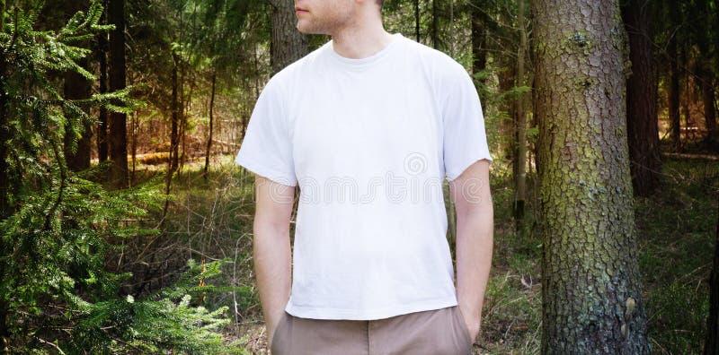 Grabben i den tomma vita t-skjortan, ställning i grön skogbakgrund, åtlöje upp royaltyfri fotografi