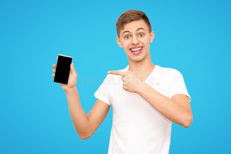 Grabben i den vita T-tröja annonserar telefonen som isoleras på en blå bakgrund, mannen, rymmer telefonskärmen i kameran arkivbilder