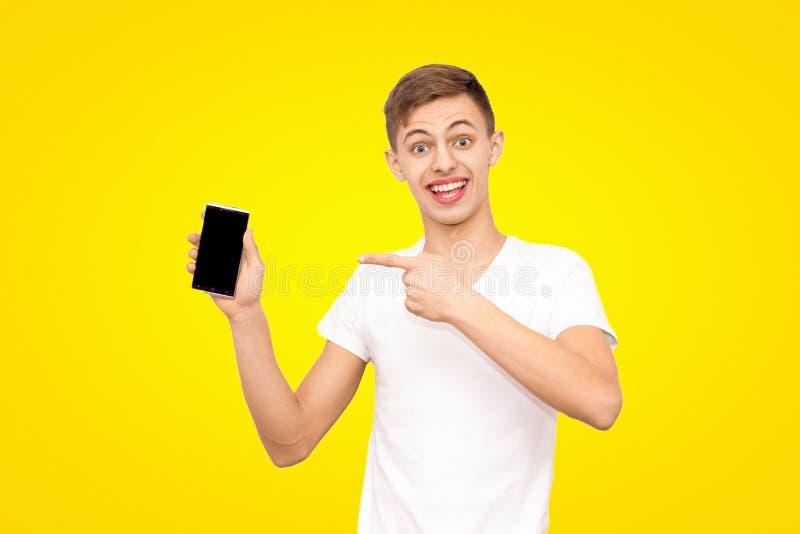 Grabben i den vita T-tröja annonserar telefonen som isoleras på en gul bakgrund, mannen, rymmer telefonskärmen i kameran royaltyfria foton