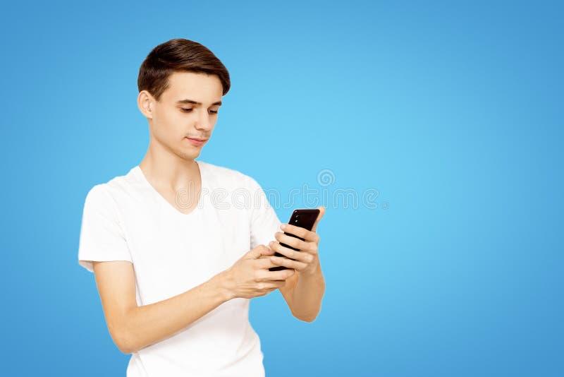 Grabben i den vita T-tröja med telefonen på en blå bakgrund Ung tonåring som ordineras i sociala nätverk arkivbilder