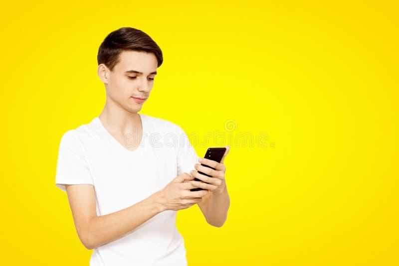 Grabben i den vita T-tröja med telefonen på en gul bakgrund Ung tonåring som ordineras i sociala nätverk arkivbilder
