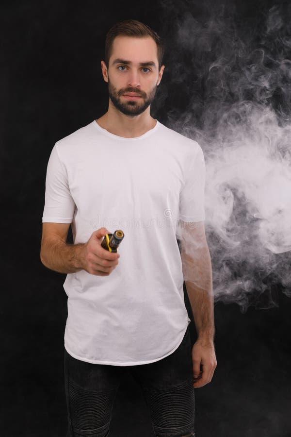 Grabben i den vita T-tröja på en svart bakgrund med en elektronisk cigarett arkivfoton