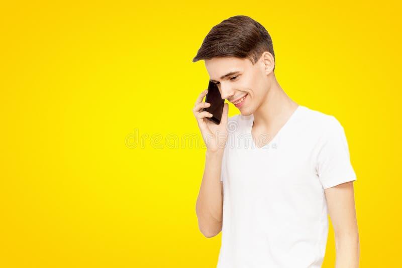 Grabben i den vita T-tröja som talar på telefonen på en gul isolerad bakgrund, snacksalig ung man royaltyfria foton