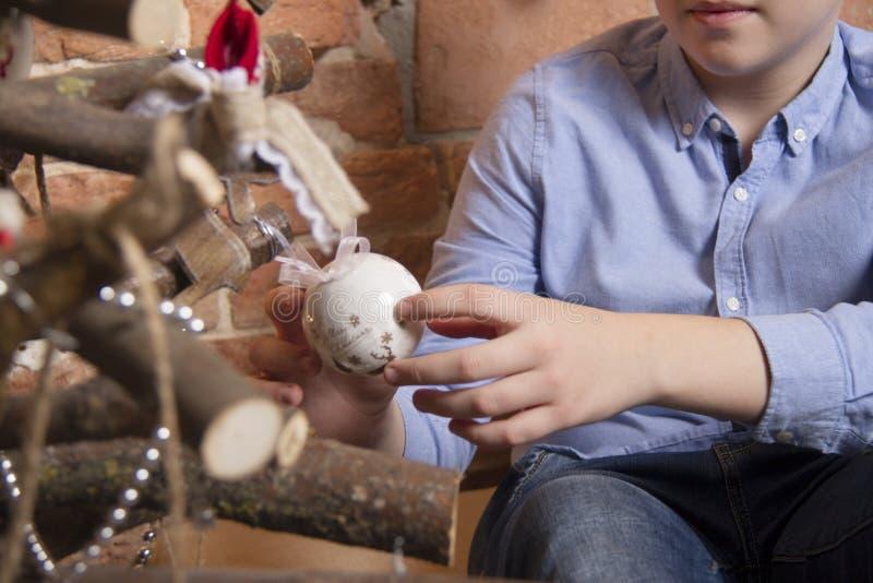 Grabben i en blå skjorta sitter nära ett idérikt träd för nytt år från filialer och rymmer händer en vit boll arkivbild