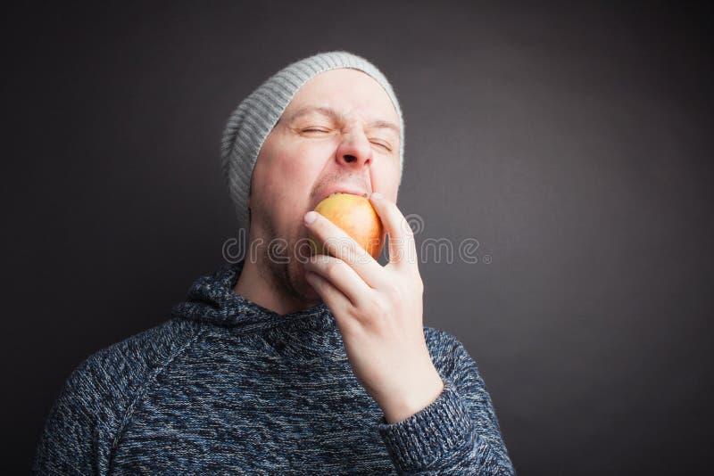 Grabben i hatten äter en röda Apple på en svart bakgrund i studion royaltyfria foton