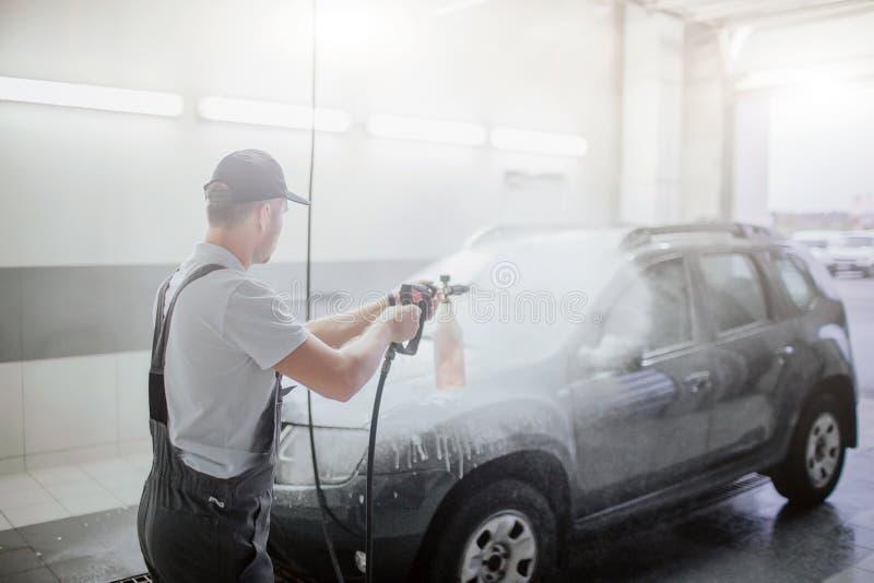 Grabben i likformig står framme av bilen och tvättar den med vatten som går från den böjliga slangen Den svarta bilen täckas med royaltyfria foton