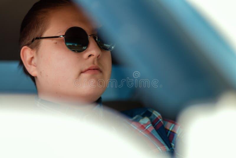 Grabben i solglas?gon som sitter i bilk?rningen royaltyfria foton