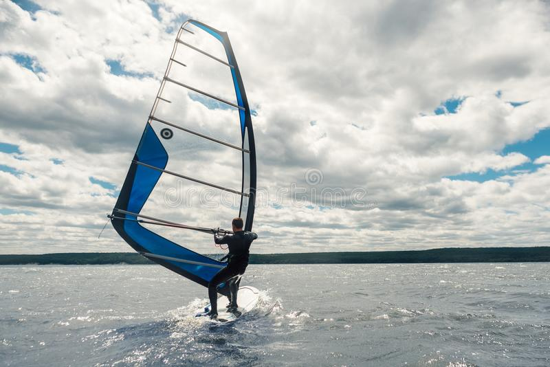 Grabben i waggonen simmar på vindsurfa på sjön royaltyfria bilder