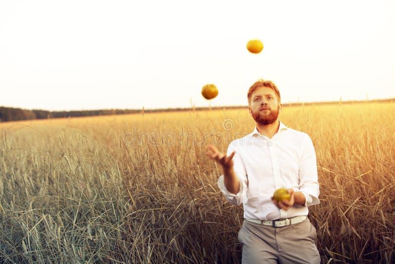 Grabben jonglerar med äpplen arkivfoto