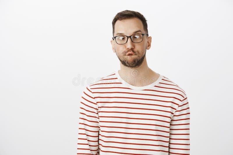 Grabben kan inte växte upp Stående av den roliga skämtsamma europeiska mannen med borstet i exponeringsglas som skelar och ser nä arkivfoto