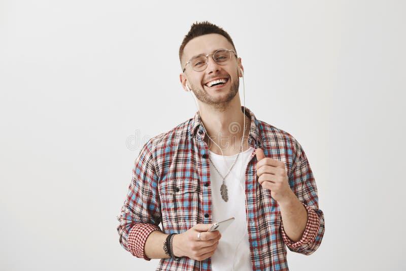 Grabben kontrollerar ut sången av sångaren hans vän möjlig för att lyssna Gullig spenslig man i exponeringsglas som ler med nöjt arkivfoto
