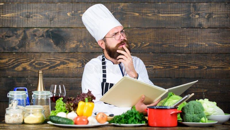 Grabben läste bokrecept Begrepp för kulinariska konster Mannen lär recept försök något som är ny Matlagning på min mening Förbätt arkivbild