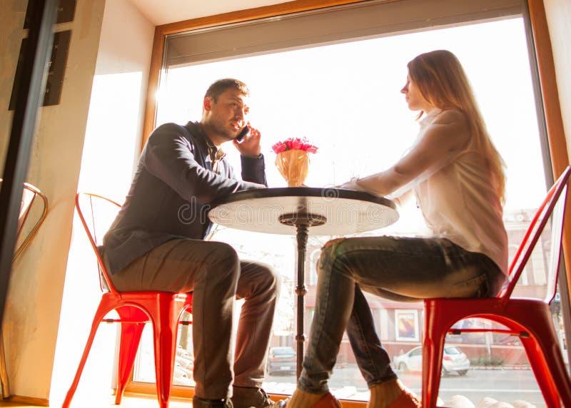 Grabben med en flicka i ett kafé på dag för St-valentin` s, en grabb ger a royaltyfri bild