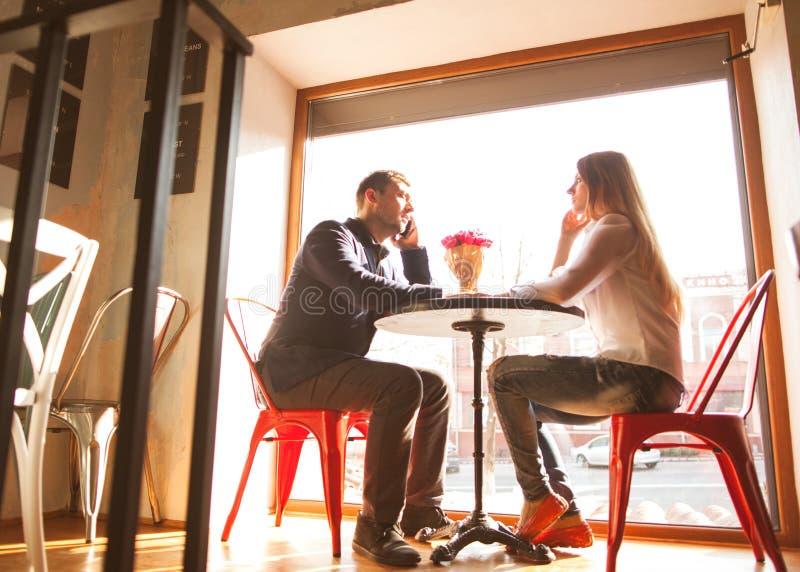Grabben med en flicka i ett kafé på dag för St-valentin` s, en grabb ger a royaltyfria bilder