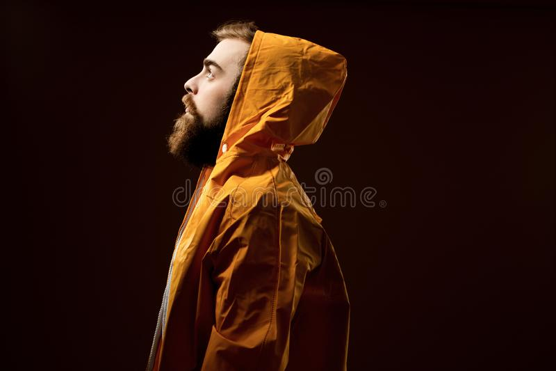 Grabben med ett ikl?dda sk?gg och mustasch en gr? t-skjorta och ett gult omslag med en huv st?r p? en brun bakgrund fotografering för bildbyråer