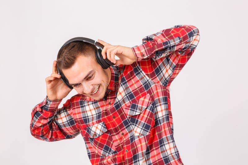 Grabben med ett leende rymmer på till hörlurarnärbilden på en grå bakgrund royaltyfria bilder