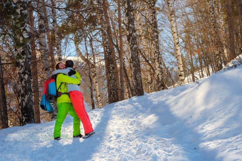 Grabben med flickan går i den soliga dagen för vinterskogen i bergen royaltyfri bild