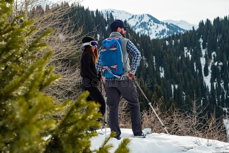 Grabben med flickan i vintern i bergen Utomhus- turism för vinter på snöskor fotografering för bildbyråer