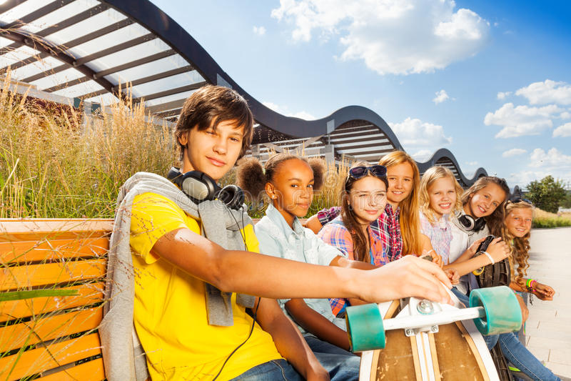 Grabben med flickor sitter på bänk och rymmer skateboarden arkivbild