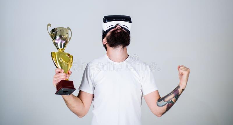 Grabben med VR-exponeringsglas segrade mästerskapet, håll i guld- bägare för hand Man med skägget i VR-exponeringsglasvinnaren, g arkivfoton