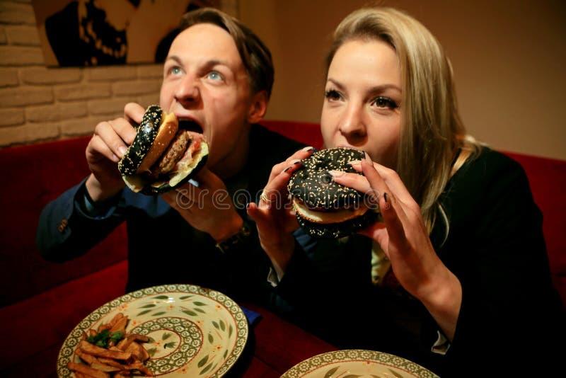 Grabben och flickan äter ostburgaren med svart bröd, nötköttlilla pastejen, bacon, tomater och stycken av ost, påklädd fotografering för bildbyråer