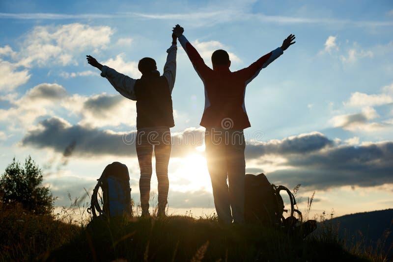 Grabben och flickan för bakre sikt som innehavet räcker höjdpunkt, lyftte deras händer upp mot solnedgång i berg arkivfoto