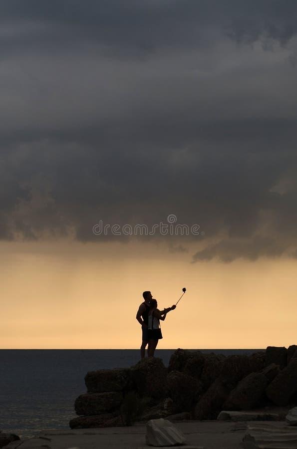 Grabben och flickan i ljuset Ta en selfie mot havet arkivfoto