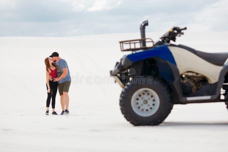 Grabben och flickan kysser i öknen, deras kvadratcykel står bredvid dem och att ha gyckel och tycka om, ett förälskat par royaltyfri fotografi