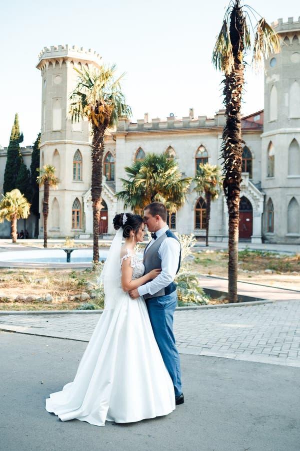 Grabben och flickan ler p? de Klassiska unga brölloppar arkivfoton
