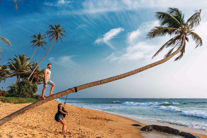 Grabben och flickan nära en palmträd på stranden möter solnedgången fotografering för bildbyråer