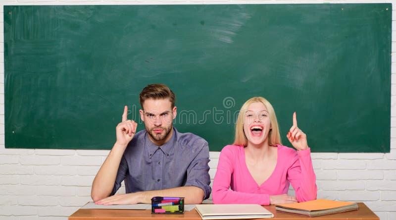 Grabben och flickan sitter på skrivbordet i klassrum Korrekt svar på deras mening Studera i högskola eller universitet Applicera  arkivbild